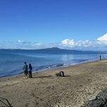 Photo taken at Mairangi Bay Beach by Simon B. on 6/29/2013