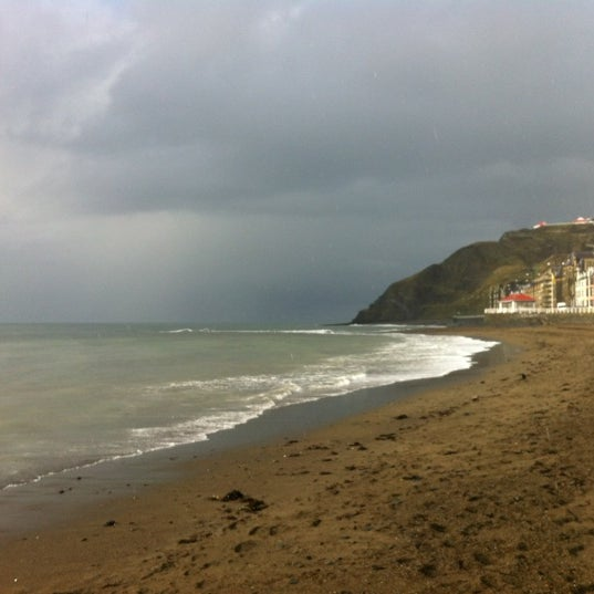 Photo taken at Aberystwyth Beach by Dan S. on 3/17/2012